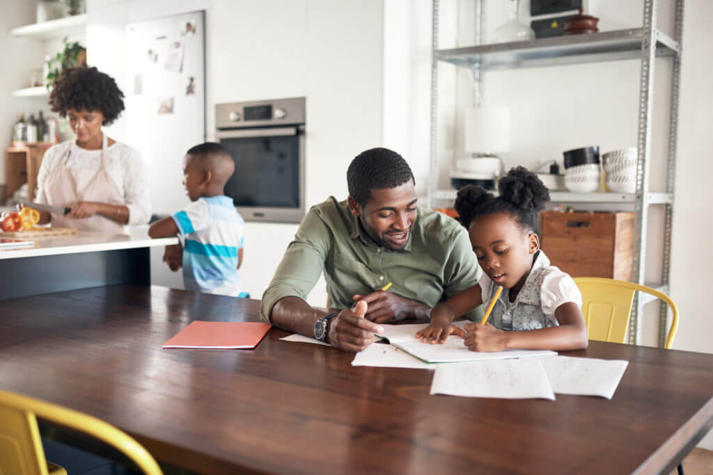 Shot of young man helping his daughter with her homework while her mother cooks in the background